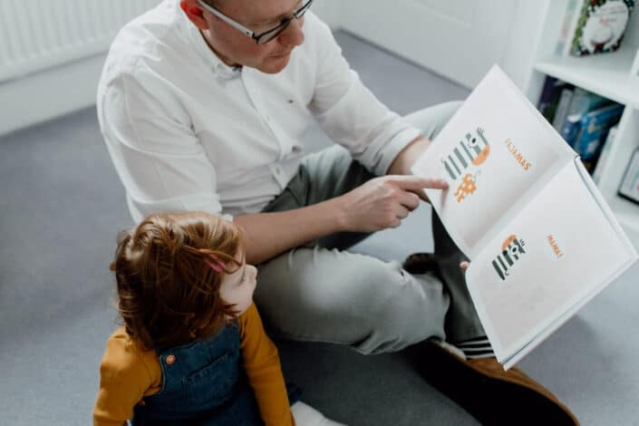Dad is sitting on the floor and reading book to his toddler daughter. Family photographer in Basingstoke, Hampshire. Ewa Jones Photography