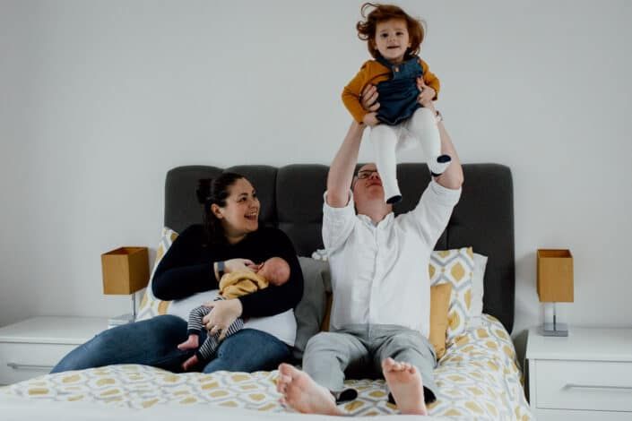 Mum and dad are sitting on the bed. Mum is holding newborn baby and dad is throwing in the air his toddler daughter. They are all smiling. Newborn baby lifestyle photography in Basingstoke, Hampshire. Ewa Jones Photography