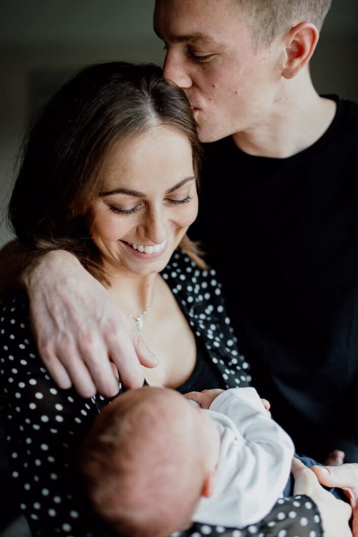 Dad kissing mum and mum is holding a newborn baby. Newborn baby photoshoot in Hampshire. Ewa Jones Photography