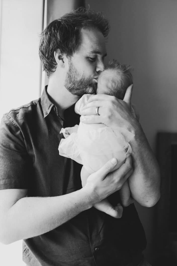 Dad is kissing his newborn baby girl on her head. He is standing next to the window and the picture is in black and white. Newborn photo session in Hampshire. Ewa Jones Photography