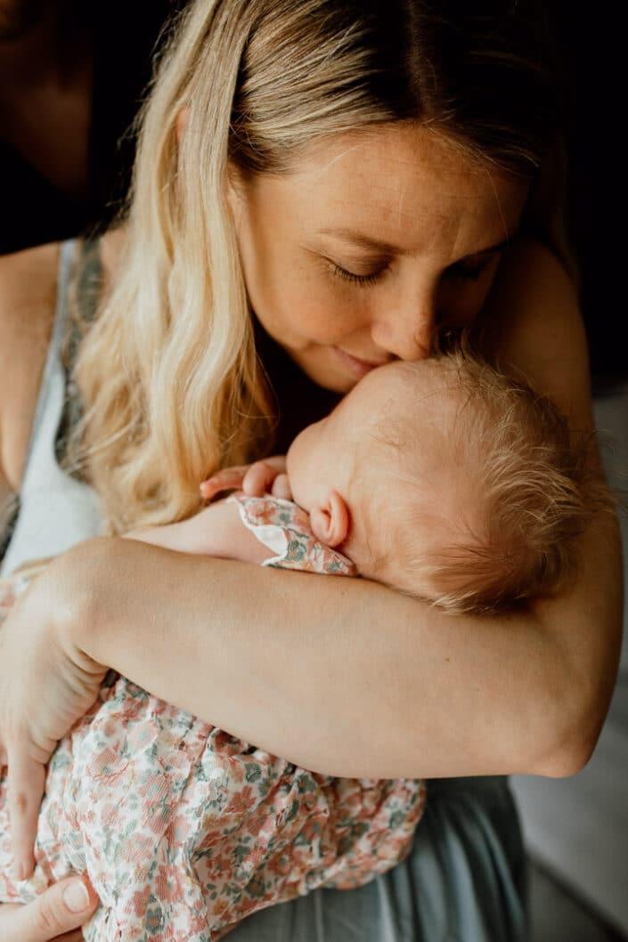 Mum is holding her newborn baby close to her chest. Mum is leaning down and smelling her newborn baby head. Newborn baby photographer in Hampshire. Ewa Jones Photography