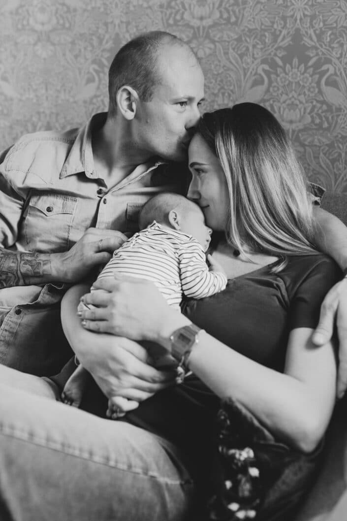 Mum and dad are sitting on the sofa and dad has his hand wrapped around mum. Mum is holding her newborn baby girl and baby girl is sleeping. Newborn photography in Hampshire. Ewa Jones Photography