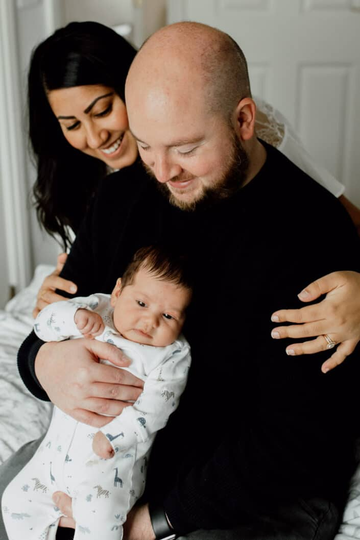 Mum and dad are on the bed and mum is holding dad lovingly. Dad is holding his newborn baby boy. Newborn baby photography in Hampshire. Ewa Jones Photography