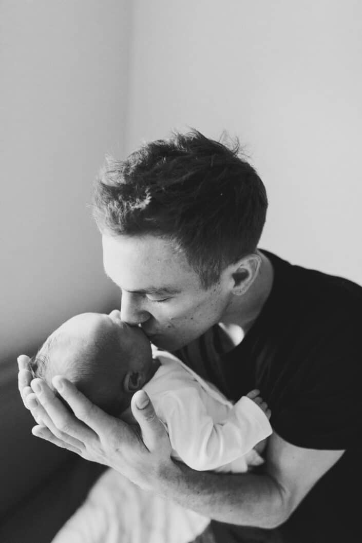 Dad is sitting on the bed and kissing his newborn baby. Black and white photography. Hampshire newborn photoshoot. Ewa Jones Photography