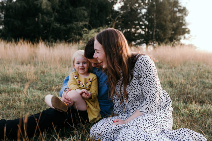 Mum and dad sitting on the grass with daughter. Sunset family photoshoot in Basingstoke. Hampshire. Ewa Jones Photography