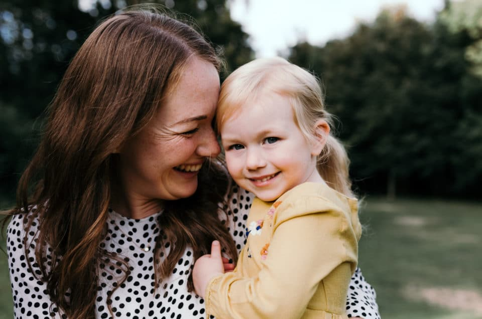 Mum holding girl smiling to her. Sunset family photoshoot in Basingstoke