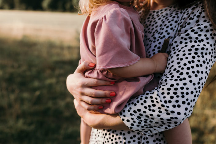 Mum holding a girl in the field. Detail shoot during family photoshoot in Basingstoke. Hampshire. Ewa Jones Photography