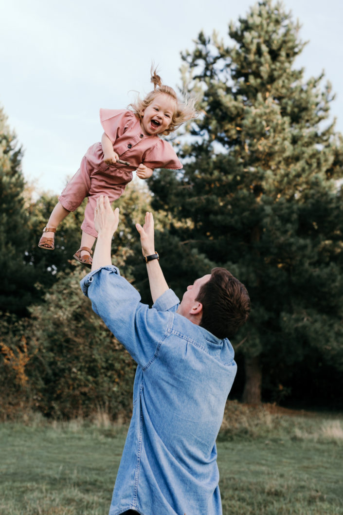 Dad throwing girl into the air. Girl is laughing. Family photoshoot in Basingstoke. Ewa Jones Photography
