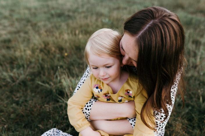 Happy girl held by her mum. Girl is wearing a yellow dress. Family photoshoot in Basingstoke. Ewa Jones Photography