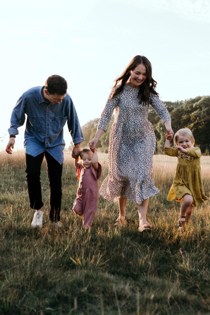 Family running on the field during sunstet family photoshoot in Basingstoke. Hampshire. Ewa Jones Photography