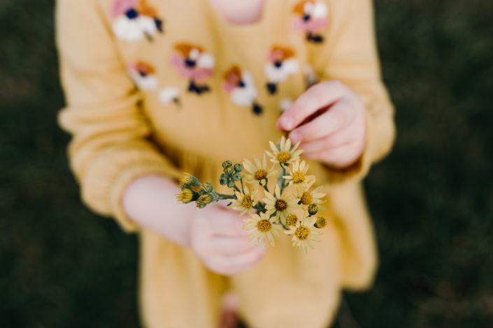 Girl in yellow dress in holding yellow flowers during sunset family photpshoot in Basingstoke. Hampshire. Ewa Jones Photography