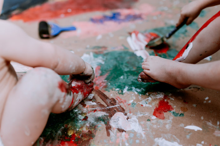 SIsters palying with paint and painting feet by Ewa Jones Photography