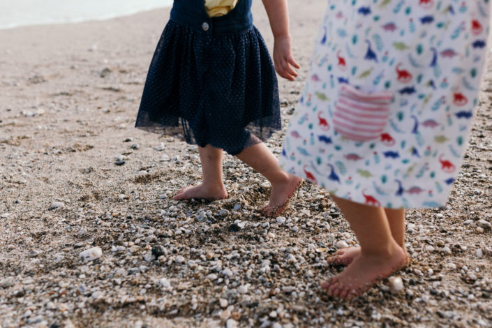 Girls feet walking on the beach by Ewa Jones Photography