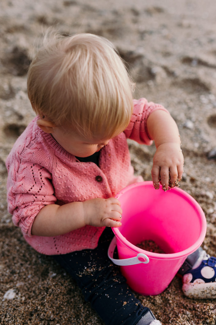 Girl playing with bucket and sand by Ewa Jones Photography | Hampshire Photography