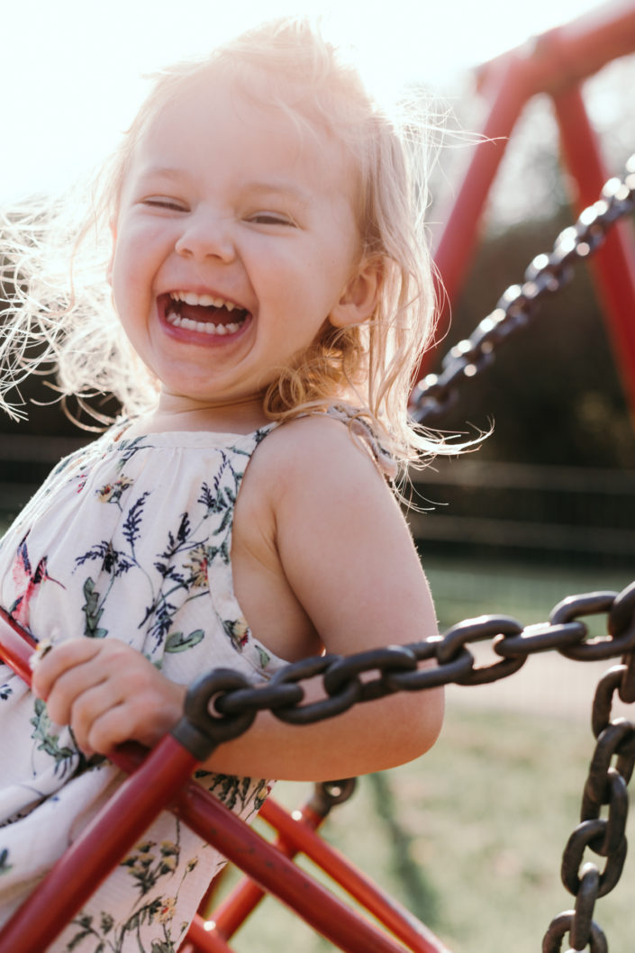 Girl on the swing smiling by Ewa Jones Photography