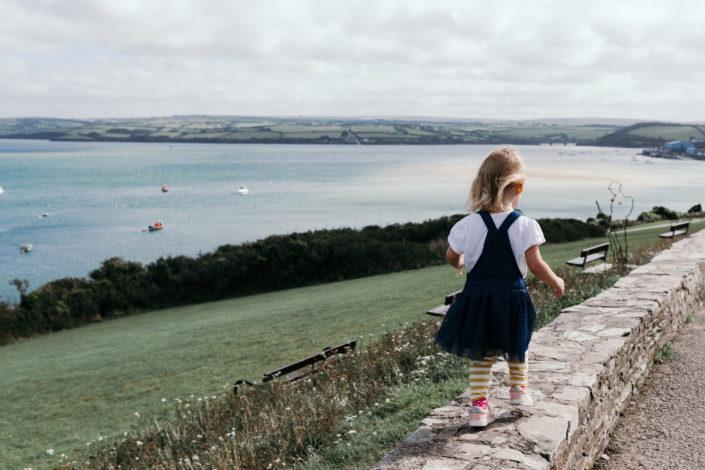 Girl walking on the wall in Padstow overlooking Doom Bar by Ewa Jones Photography