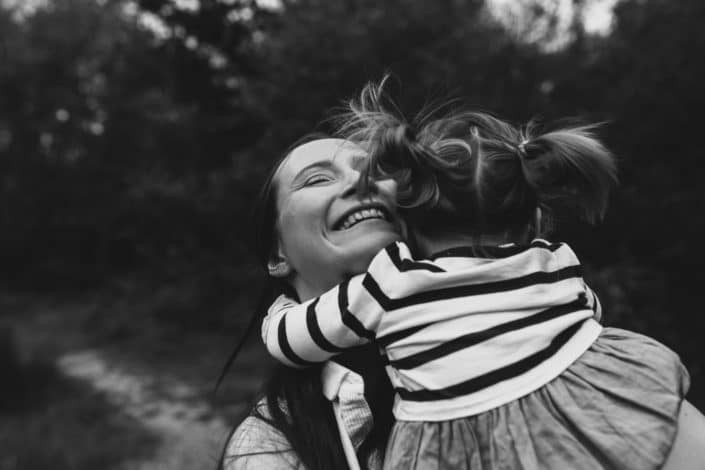 Mum is having cuddles with her daughter and smiling happily. family lifestyle photography in Hampshire. Ewa Jones Photography.