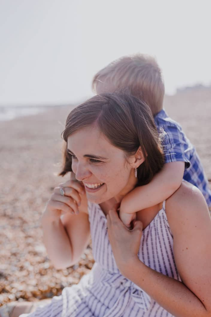 Mum is sitting on the beach and laughing. Her little boy has his arms wrapped around his mum neck. Lovely mother and son connection. Family lifestyle photography in Hampshire. Ewa Jones Photography