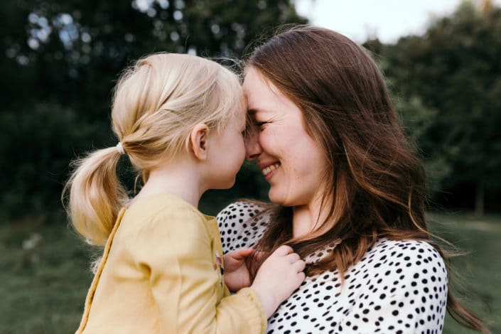 Mum is looking at her daughter and smiling at her. They are touching noses. Girl is wearing a yellow dress. Mother and daughter time. Family photography in Hampshire. Ewa Jones Photography