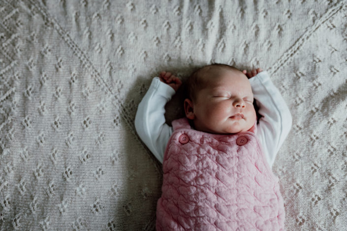 Newborn baby sleeping on the bed with hands up. My six-must have poses for a newborn photoshoot.Baby sleeping on a lovely blanket. Newborn photography in Hampshire. Ewa Jones Photography