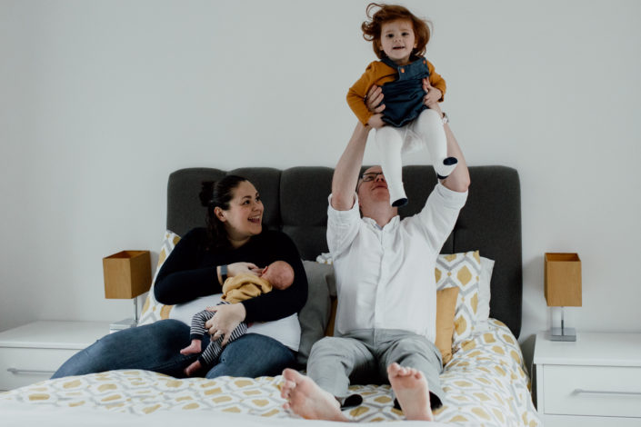 Mum, dad, older sister and little newborn are on the bed. Mum is looking up at the older daughter laughing when dad is throwing girl into the air. Lifestyle newborn photography in Hampshire. Ewa Jones Photography