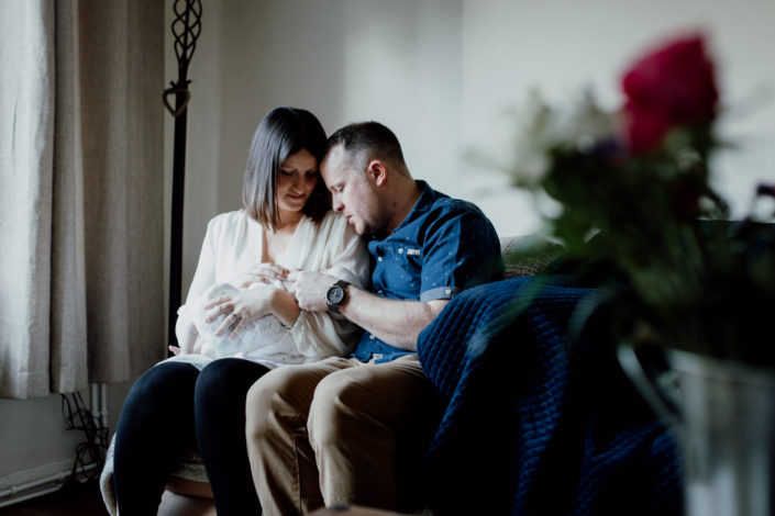 Mum and dad are sitting on the sofa and looking lovingly at their newborn baby. Lifestyle newborn photography in Basingstoke. Ewa Jones Photography