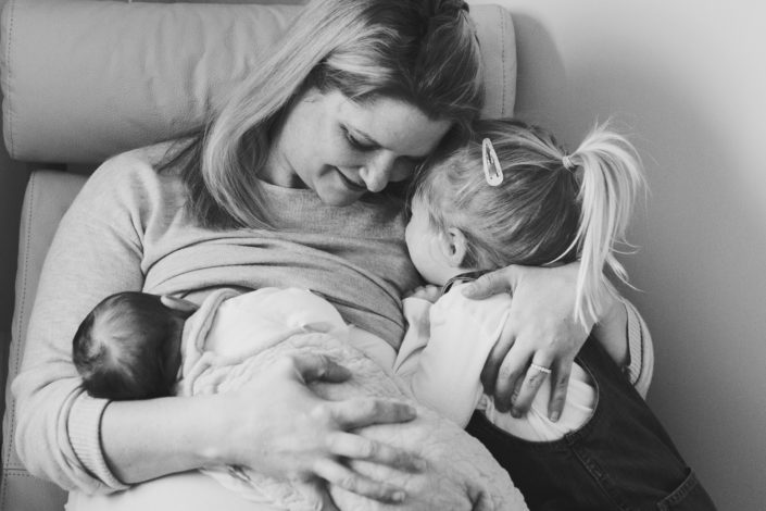 Mum is sitting on the chair and breastfeeding newborn baby. Mum is at the same time cuddling her older daughter. Newborn lifestyle family photography in Hampshire. Ewa Jones Photography