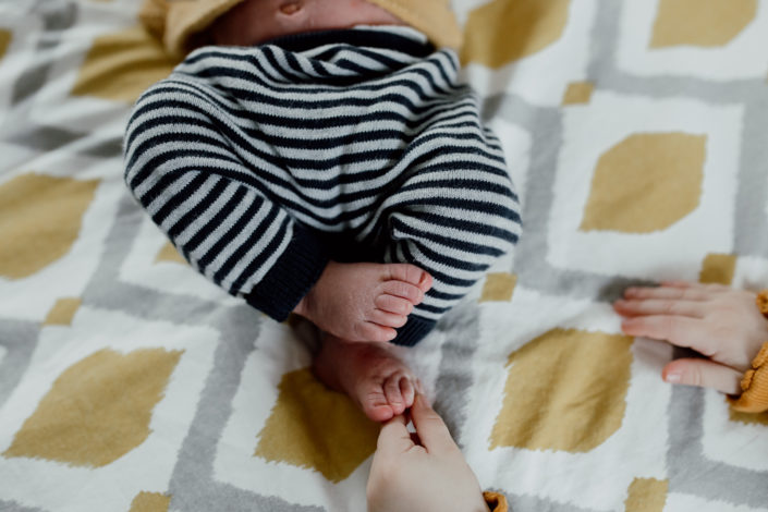 Newborn feet details. Older sibling is touching newborn baby brother feet. Newborn photoshoot in Hampshire. Ewa Jones Photography