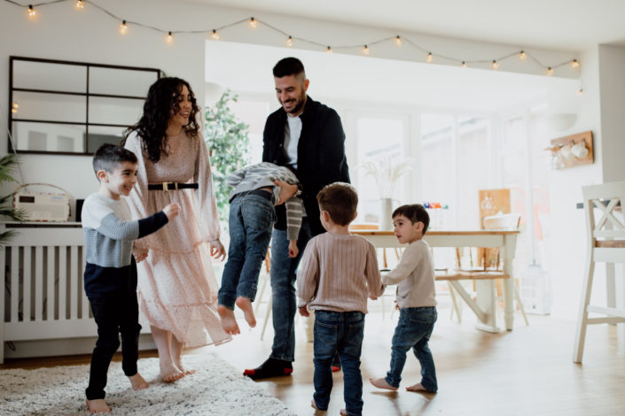 Mum and dad are dancing in the kitchen with their four boys. Dad is lifting up one boy. Other boys are dancing and laughing. Family lifestyle photographer in Hampshire. Ewa Jones Photography