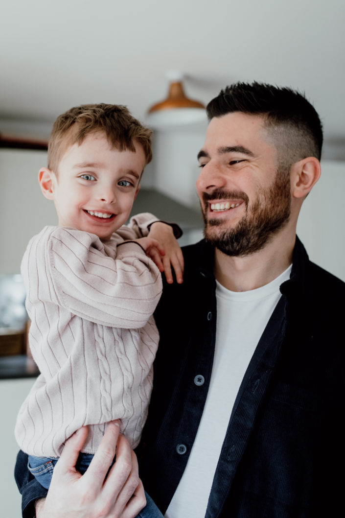 Dad is holding his little son and looking at him. on is wearing a light color jumper and dad is wearing black shirt with white t-shirt. Both are happy. Family lifestyle photography. Ewa Jones Photography
