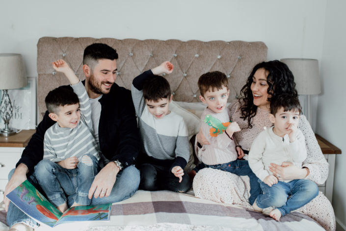 Family of six is sitting on the bed and looking at each other. Two boys are raising their hands and mum and dad are lovingly watching them. Family photography in Hampshire. Ewa Jones Photography