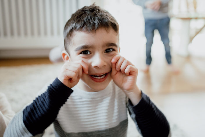 Boy is laughing and holding his hands on his cheeks. Family lifestyle photographer in Hampshire. Ewa Jones Photography