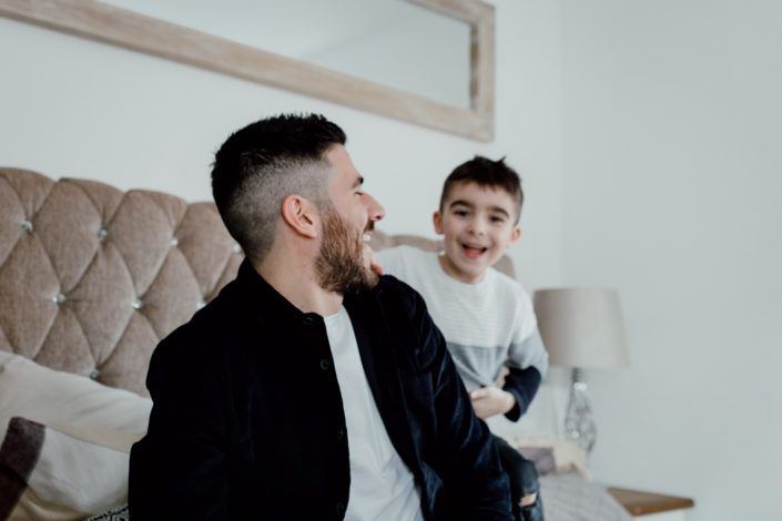 Dad and son are sitting on the bed and laughing at each other. Candid family moment. Izzo Family. Ewa Jones Photography