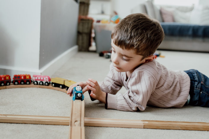 Boy is laying on the floor and playing with trains and train track. Family photography. Izzo Family. Ewa Jones Photography