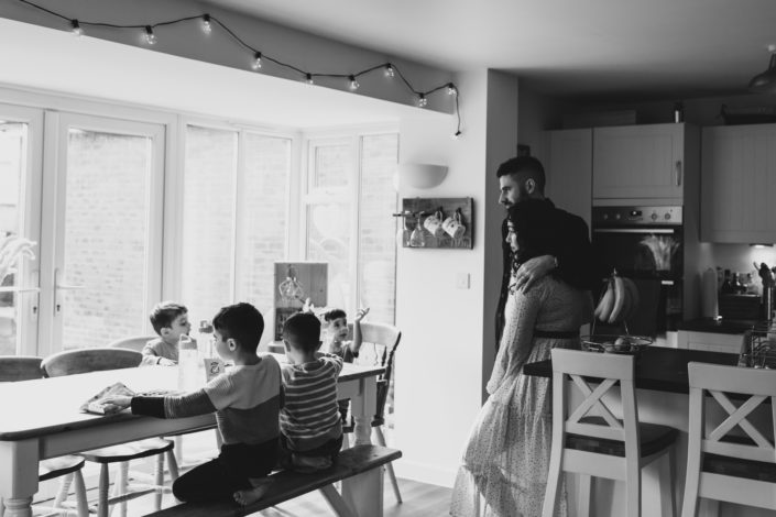 Mum and dad are standing in the kitchen looking at their boys eating lunch. Boys are sitting on the bench and eating. Candid family moment. Family photographer ins Hampshire. Ewa Jones Photography