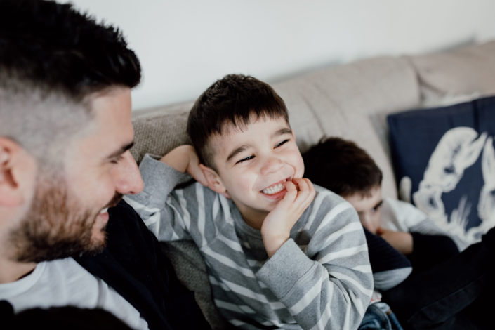 Dad is looking at his son and boy is smiling. Boy is wearing grey stripy jumper. Family photographer in Hampshire. Ewa Jones Photography