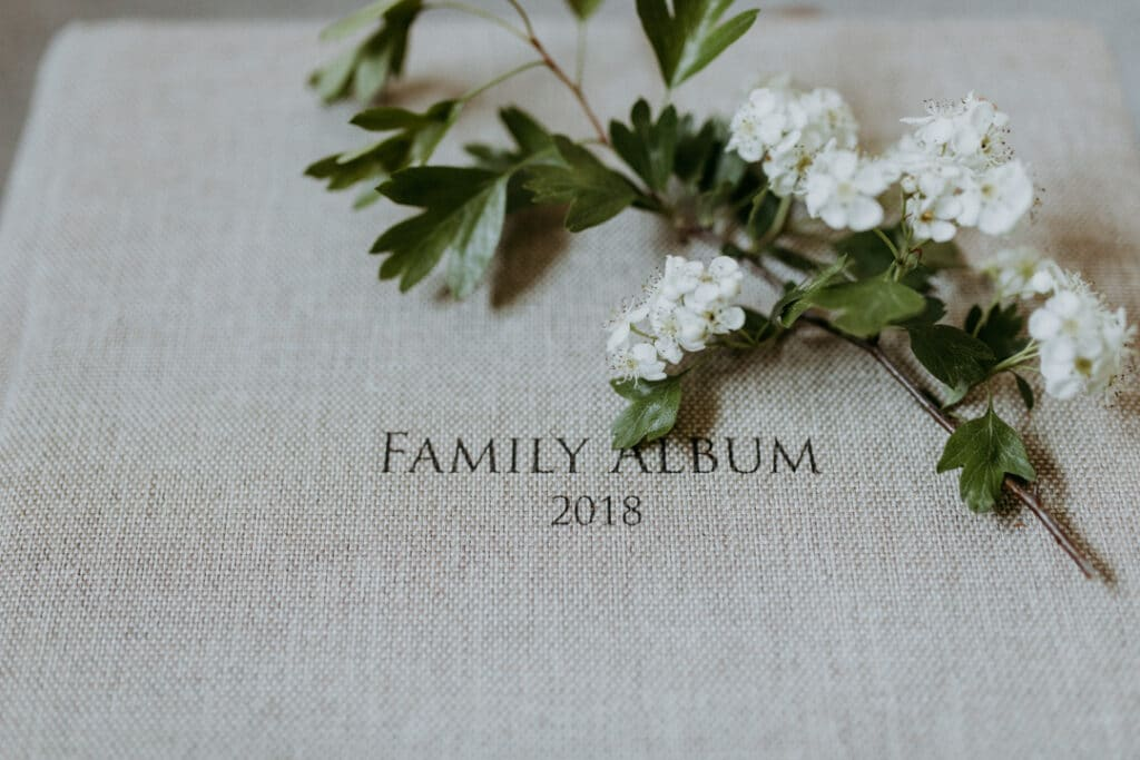 Photo album in light grey textile finish with a white flower laying on the album. Words on the album are saying Family Album 2018. Family photography in Basingstoke. Ewa Jones Photography