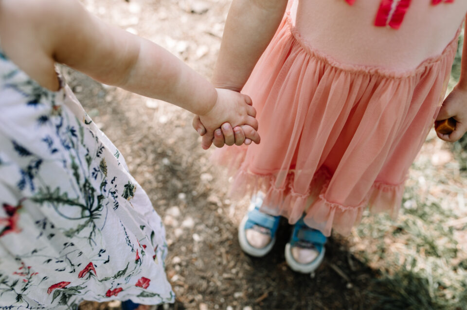 Two sisters are holding hands. One is wearing pink dress and blue trainers and another is wearing a white dress with colorful flowers. Family photographer in Basingstoke. Ewa Jones Photography