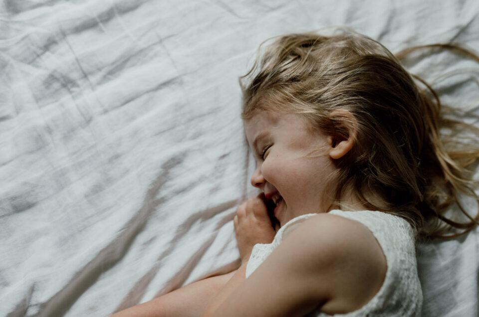 Girl is laying on bed and laughing. She is wearing a white dress. Candid moment. Child's view on Covid-19. Family photographer in Basingstoke, Hampshire. Ewa Jones Photography