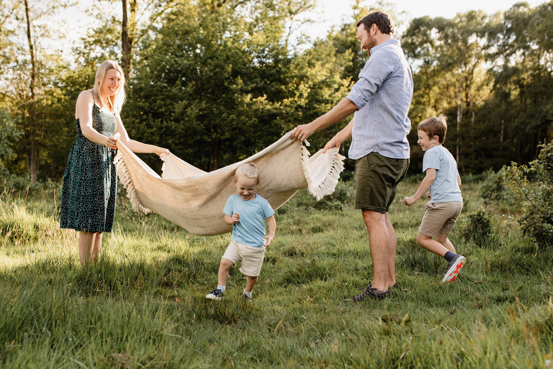 Mum and dad are holding blanket in the air and boys are running though the blanket. Family photo session during sunset. Lifestyle photography in Hampshire. Family photographer in Basingstoke. Ewa Jones Photography