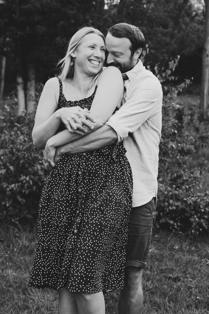 Wife and husband are hugging. Husband is kissing his wife shoulder. Couple photography. Ewa Jones Photography