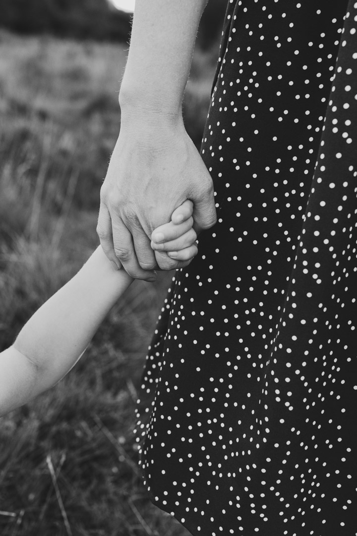 Mum is holding her son's hand. Black and white candid photography. Family photography in Hampshire. Ewa Jones Photography