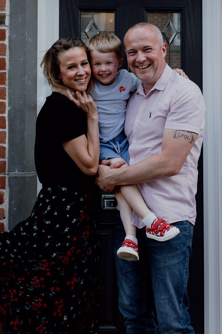Mum and dad are holding their son and smiling. family doorstep photo sessions. Family photographer in Basingstoke. Ewa Jones Photography