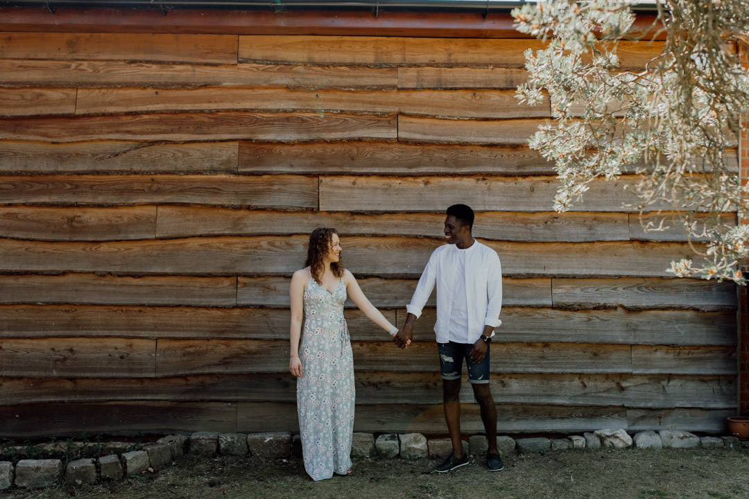 Engaged couple are standing and holding hands. They are standing in front of large wooden building. Looking at each other. Engagement photo session in Basingstoke. Ewa Jones Photography