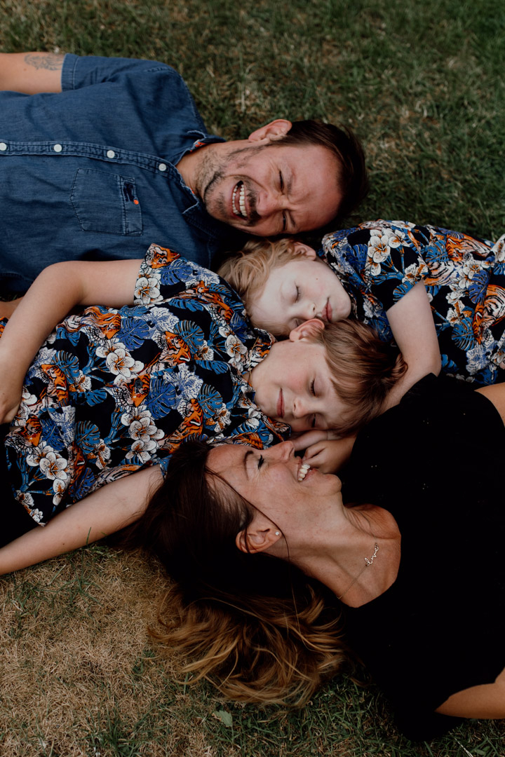 Mum, dad and two sons are laying on the grass. Mum and dad are looking at boys and both boys have their eyes closed. What to wear for a family photo session. Ewa Jones Photography
