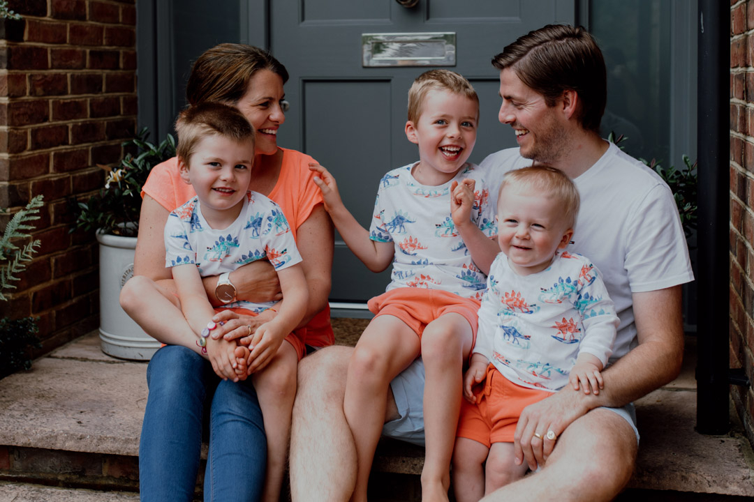 Mum dad and three boys are sitting on the step in front of their house. What to wear for a family photo session. family doorstep photo sessions. Ewa Jones Photography