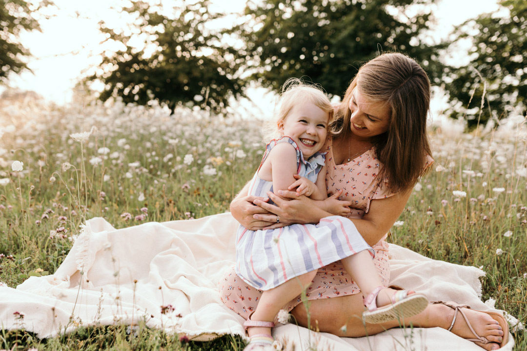 Mum and daughter are sitting on the blanket and laughing. Lovely sunset family photo session in Basingstoke. Ewa Jones Photography