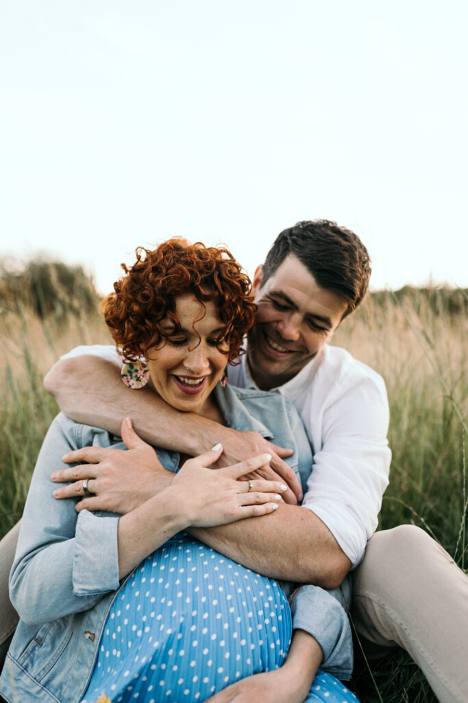 Expecting parents are sitting on the grass. Husband has his hands wrapped around his wife. Both are laughing. Maternity photo session in Hampshire. Ewa Jones Photography