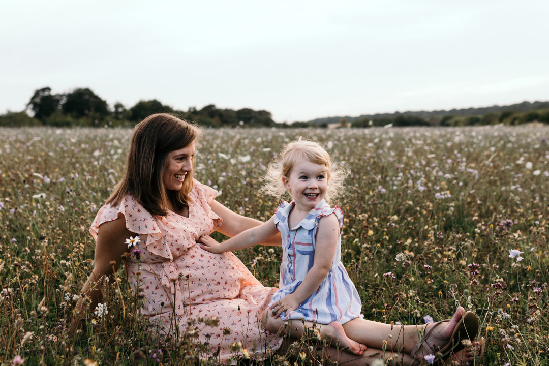 Mum and daughter are sitting on the grass. Baby kicked inside mummy tummy and little girl has a surprised face expression. Ewa Jones Photography