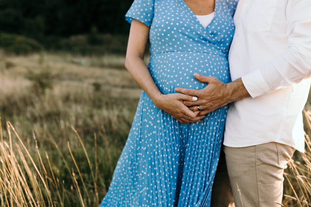 Pregnant mum is holding hands with her husband and both are holding the bump. Candid maternity photography in Hampshire. Ewa Jones Photography